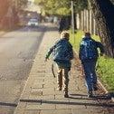 Two school kids running down a sidewalk
