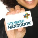 Person holding up card that says Steward Handbook